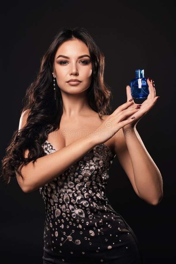 Elegant tanned woman in a beautiful dress with perfume on dark background stock image