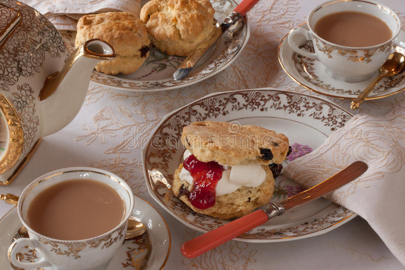 Elegant Tea and Scones. Traditional English tea with scones, cream and jam served in elegant china with gold trim royalty free stock image
