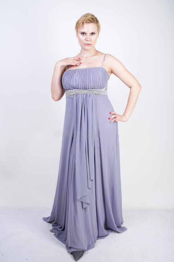 Elegant tjock kvinnlig i en grå lång klänning nätt plus formatkvinna i anseende för aftonklänning på vit studiobakgrund Kort h?r royaltyfri fotografi