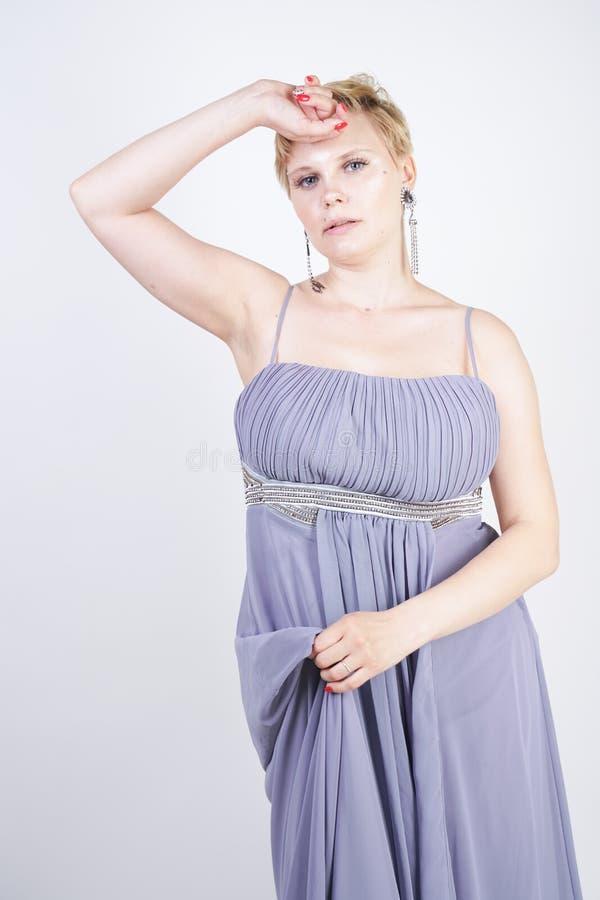 Elegant tjock kvinnlig i en grå lång klänning nätt plus formatkvinna i anseende för aftonklänning på vit studiobakgrund Kort h?r royaltyfria bilder