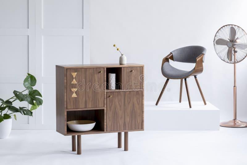 Elegant träskåp i en vardagsruminre med en guld- fan, grå stol och monsteraväxt Verkligt foto arkivbilder