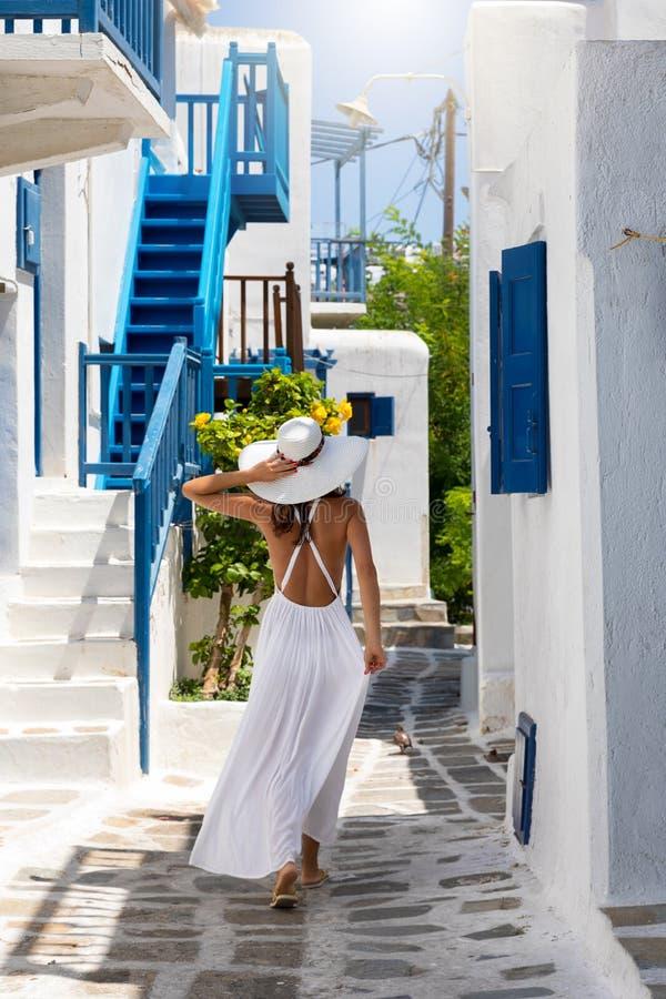 Elegant traveller woman walks through the town of Mykonos island royalty free stock image