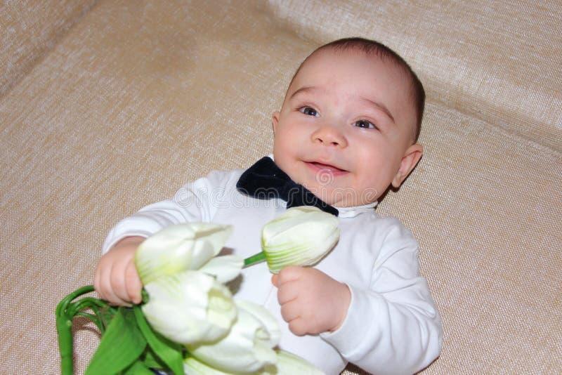 Elegant baby boy with flowers stock photo