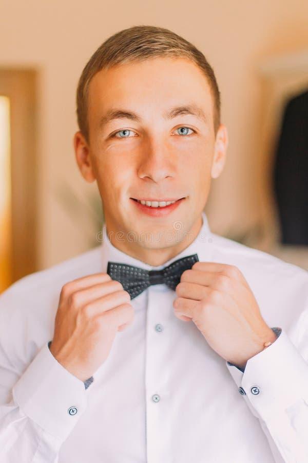 Elegant ung affärsman som poserar fixa hans svarta bowtie royaltyfria bilder