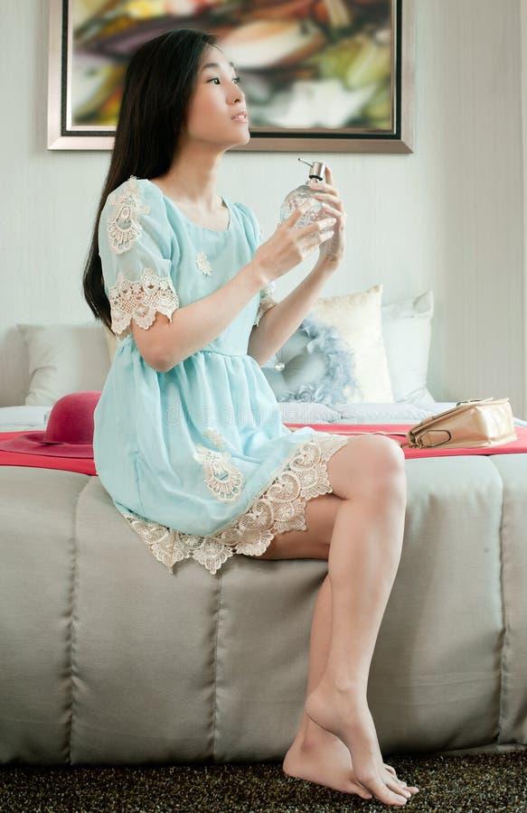 Elegant ung härlig asiatisk kvinnainnehavflaska av doft och att applicera på hennes hals i ett rum fotografering för bildbyråer