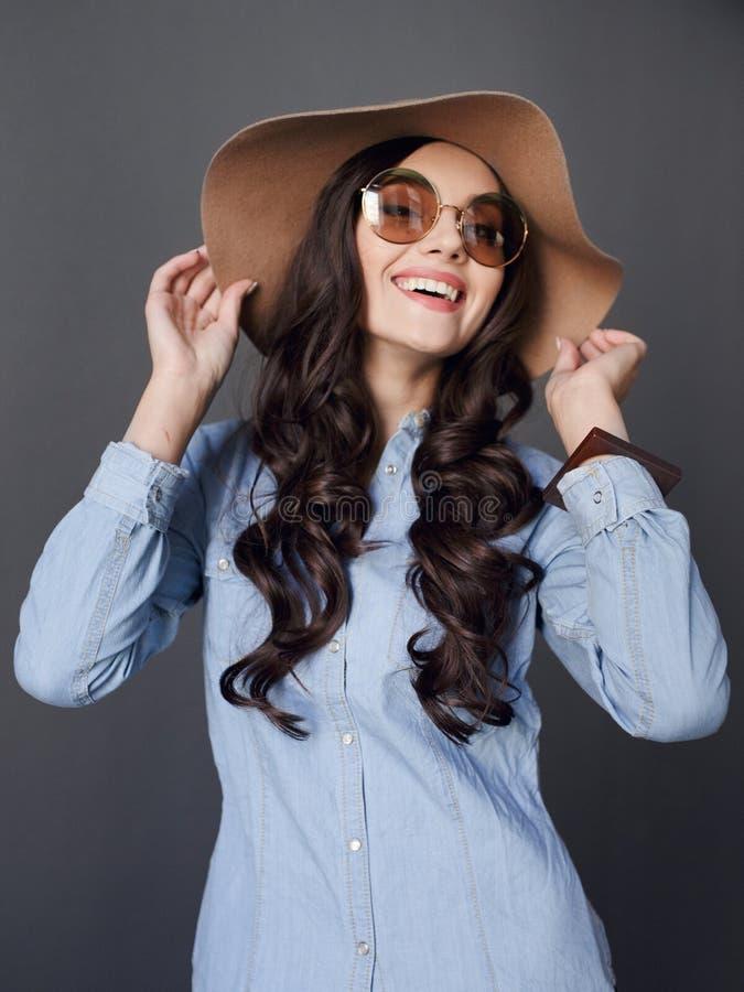 Elegant ung kvinna för lycka som poserar i studio, handlag med händer hans hatt, på en grå bakgrund royaltyfri fotografi