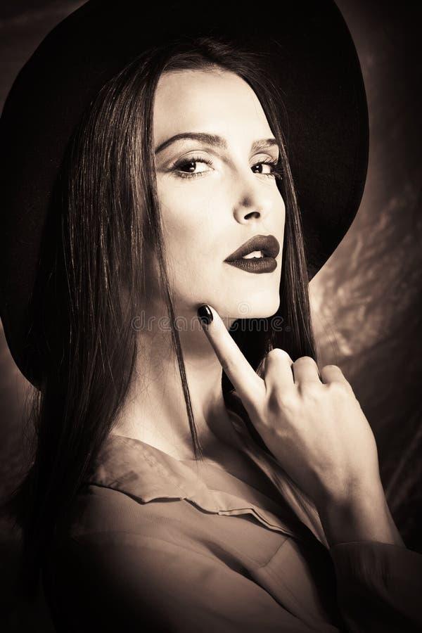 Elegant ung kvinna med hattståenden arkivbild