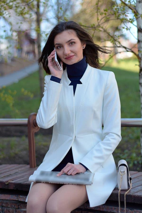 Elegant ung kvinna p? en stadsgata med en tidning i hennes handsamtal vid mobilen royaltyfri foto