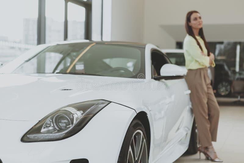 Elegant ung kvinna som köper den nya bilen på återförsäljaren arkivbilder