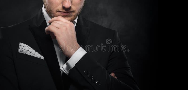 Elegant ung man i dräkten som ser rynka pannan royaltyfri foto