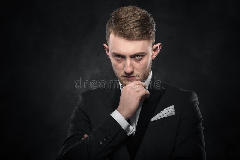 Elegant ung man i dräkten som ser rynka pannan royaltyfri fotografi