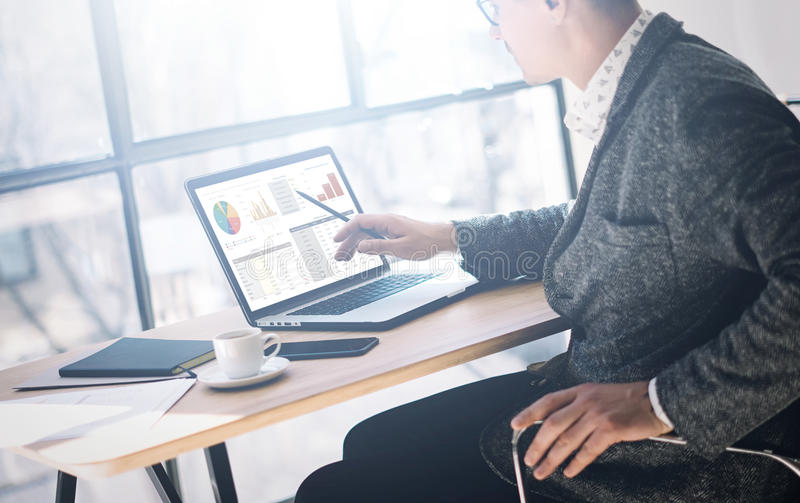 Elegant ung man i glasögon som arbetar på kontoret på bärbara datorn, medan sitta på trätabellen Affärsmananazylegrafer arkivfoton