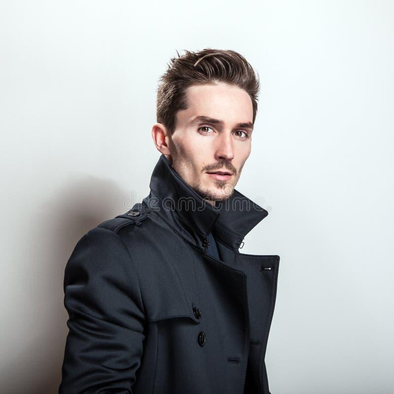 Elegant ung stilig man i långt stilfullt mörker - blått lag Manligt ta av ens kläder arkivbilder