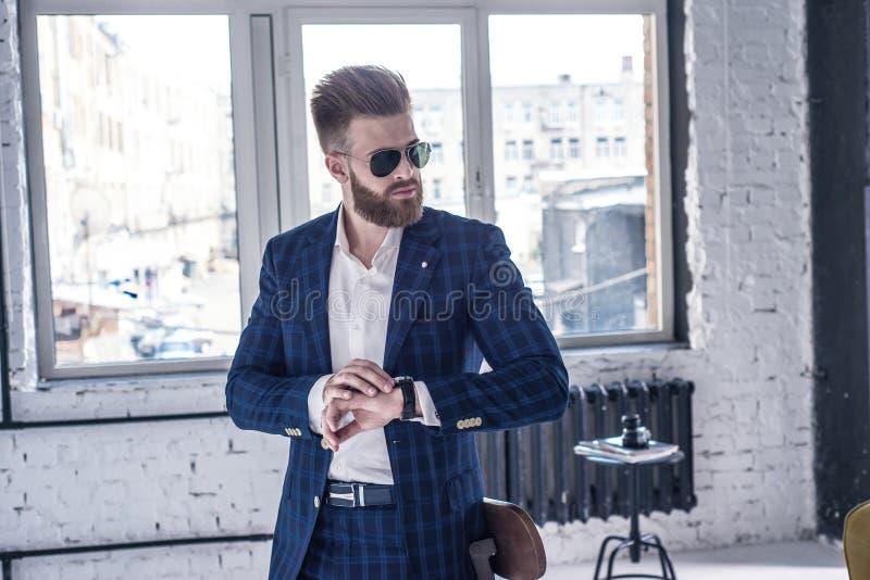 Elegant ung stilig man med bärande exponeringsglas och iakttagare för skägg Stående för vindstudiomode royaltyfri foto