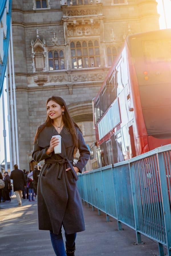 Woman walks down the Tower Bridge in London, United Kingdom. Elegant urban city woman walks down the Tower Bridge in London with a coffee in her hand, United royalty free stock photo