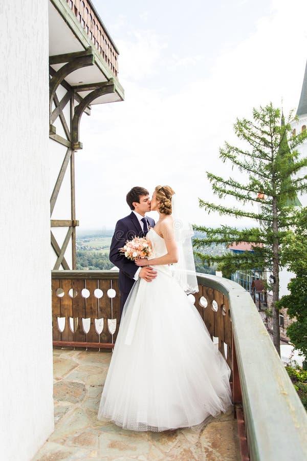 Elegant ursnyggt lyckligt brud- och brudgumanseende på balkongen arkivfoton