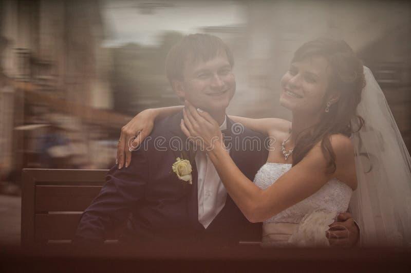 Elegant ursnyggt lyckligt brud- och brudgumsammanträde på en bänk på arkivfoto