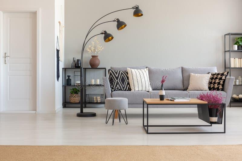 Elegant vardagsrum med den gråa soffan med mönstrade kuddar, träkaffetabell och industriell lam, med royaltyfria bilder