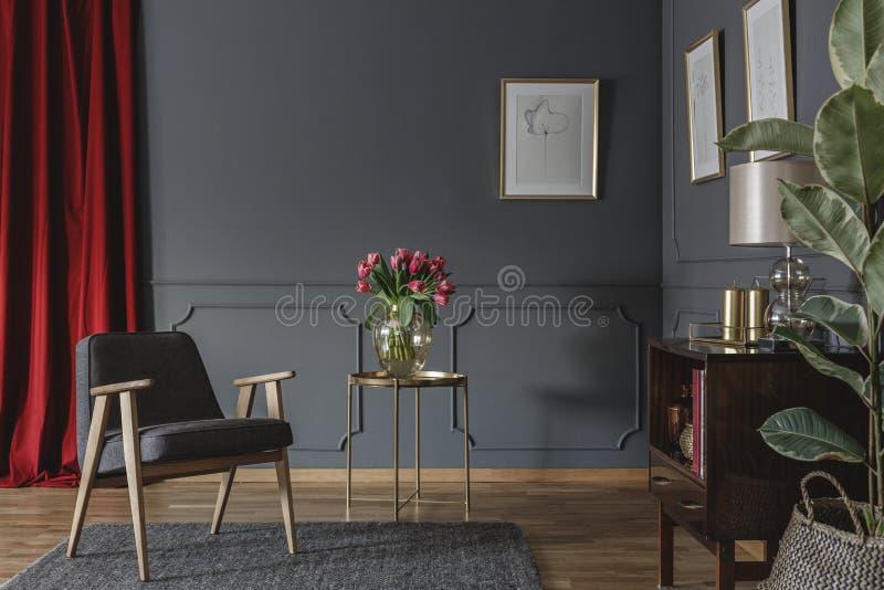 Elegant vardagsruminre med nya rosa tulpan på guld- tabl royaltyfri bild