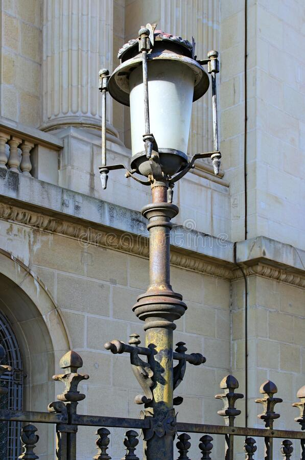 Elegant vintage lantern is lit by the bright sun. Ancient building in the background. Lamp post on a street in the Old Centre. Of Bucharest. Romania stock photo