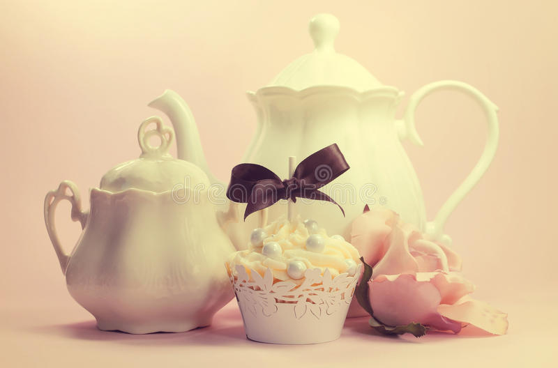 Elegant vintage retro shabby chic style afternoon or morning tea setting. With cupcake and silk rose royalty free stock image