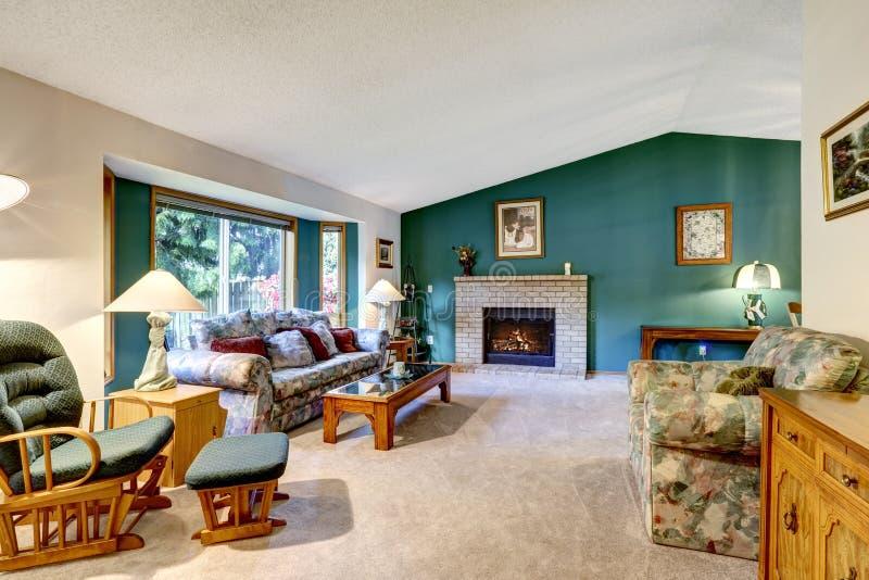 Elegant vit- och gräsplanvardagsrum Klassisk amerikansk design: tegelstenspis, gungstol och färgrik soffa royaltyfri fotografi