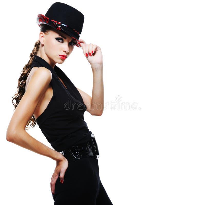 Elegant volwassen meisje in zwarte met modieuze zwarte hoed royalty-vrije stock fotografie