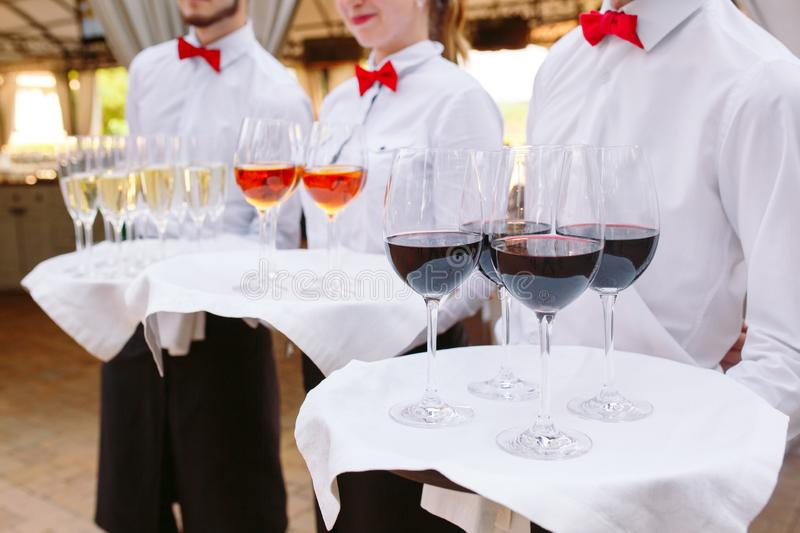Elegant waiters is holding a tray with a decorated cocktail ready to serve. stock photos
