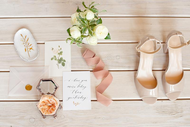 Elegant wedding bouquet with a ribbon, wedding invitation, rings and bridal shoes on tissue. royalty free stock photo