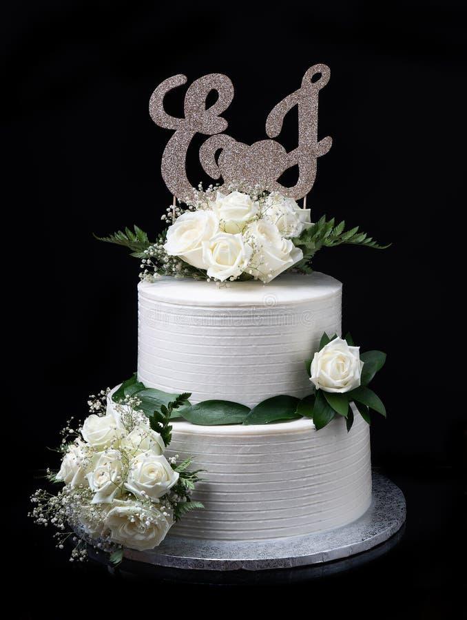 Elegant wedding cream cake, on a black background. With roses. royalty free stock image