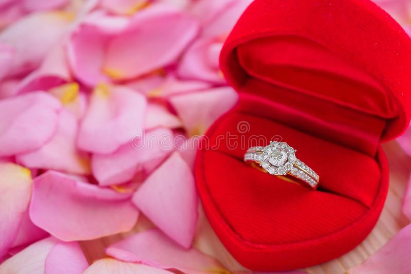 Elegant wedding diamond ring in red heart jewelry box on pink rose petal background stock photos