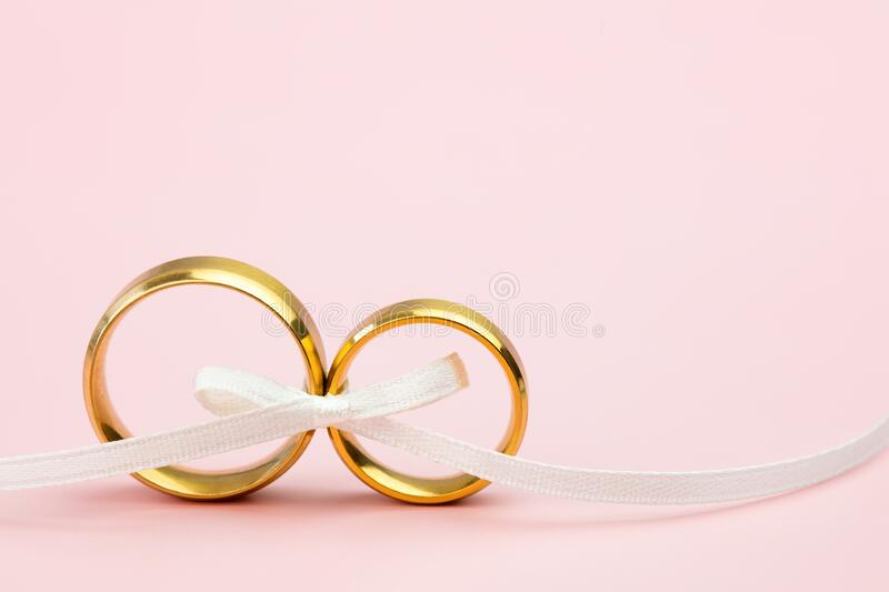 Elegant Wedding or Engagement background - pair of golden wedding rings on light pink background stock photos