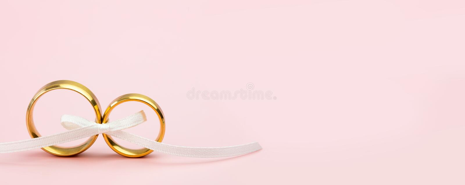 Elegant Wedding or Engagement banner background - pair of golden wedding rings on light pink background royalty free stock photos