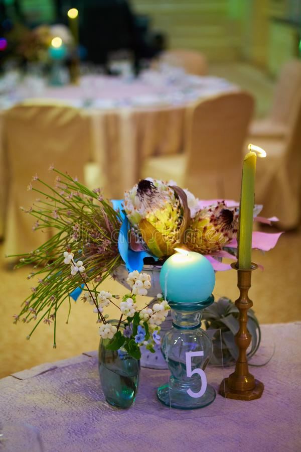 Elegant wedding guest table set for an event with candles lit stock images