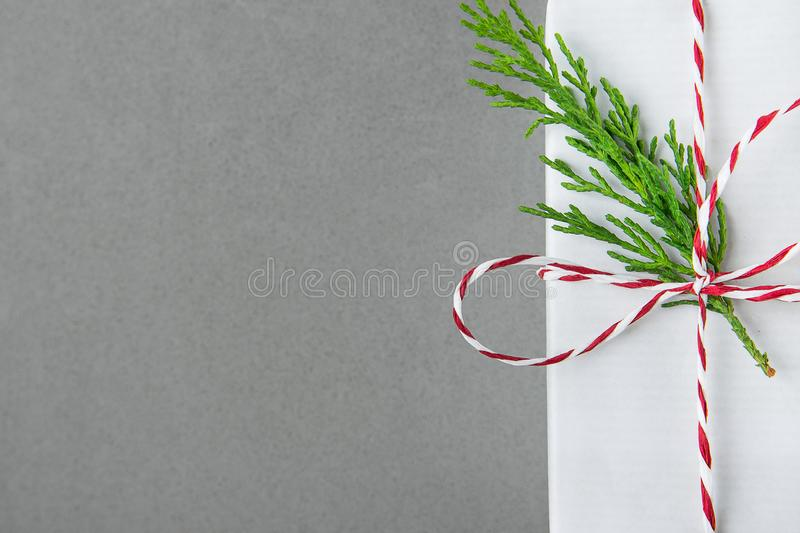 Elegant White Gift Box Tied with Red Ribbon Green Juniper Twig. Christmas New Years Presents Shopping Sale. Gray Background. Copy Space stock photos