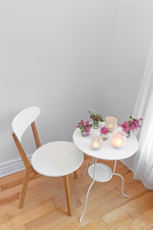 Elegant white interior with candle lights and spring flowers. Elegant home interior with white chair and table, decorated with candle lights and spring flowers stock images