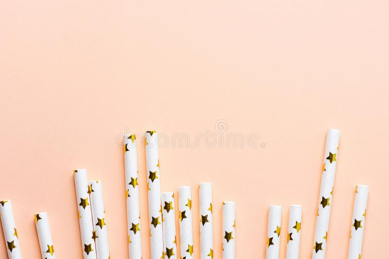 Elegant White Paper Drinking Straws with Golden Stars Pattern Scattered as Border Frame on Pink Peachy Background. Birthday Party. Fun Kids Holiday Celebration stock photos
