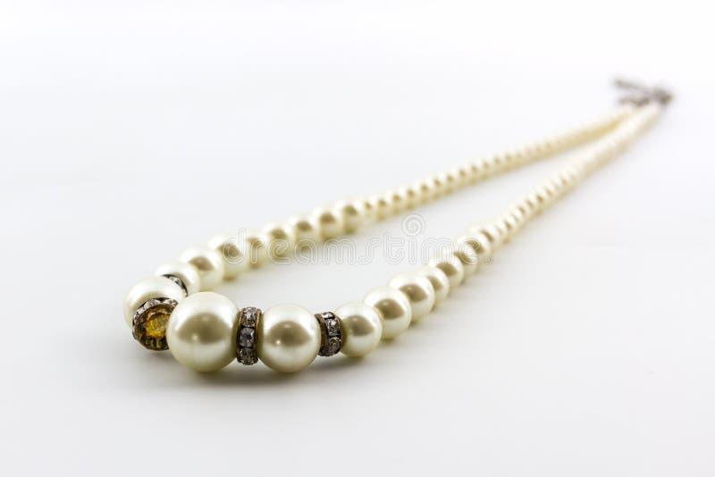 Elegant white pearl necklace. Elegant white pearl necklace on white background royalty free stock photo