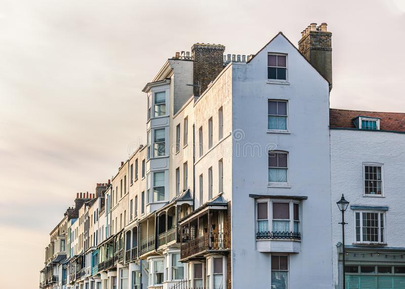 Elegant white Victorian terrace houses with ornate balconies and white rendering catching glow of the late afternoon winter sun royalty free stock photography