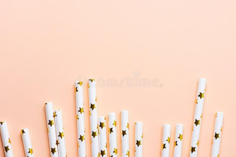 Elegant Witboek het Drinken Stro met Gouden die Sterrenpatroon als Grenskader wordt verspreid op Roze Peachy Achtergrond De parti stock foto's