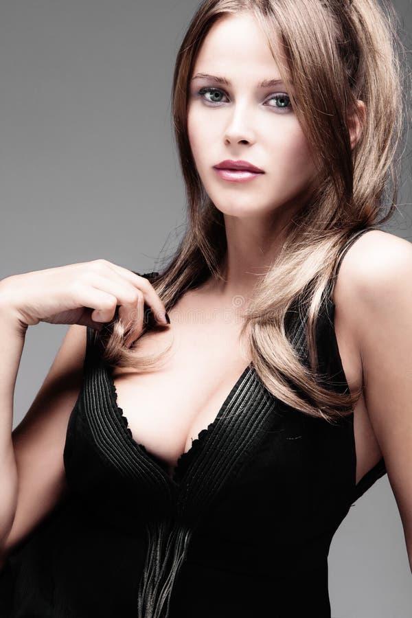 Elegant woman. Elegant young woman in provocative dress, studio shot royalty free stock image