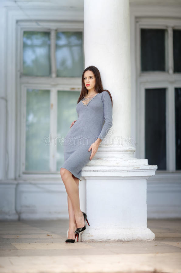 An elegant woman on the background of a large white house. The charming girl posing before the white column. stock images
