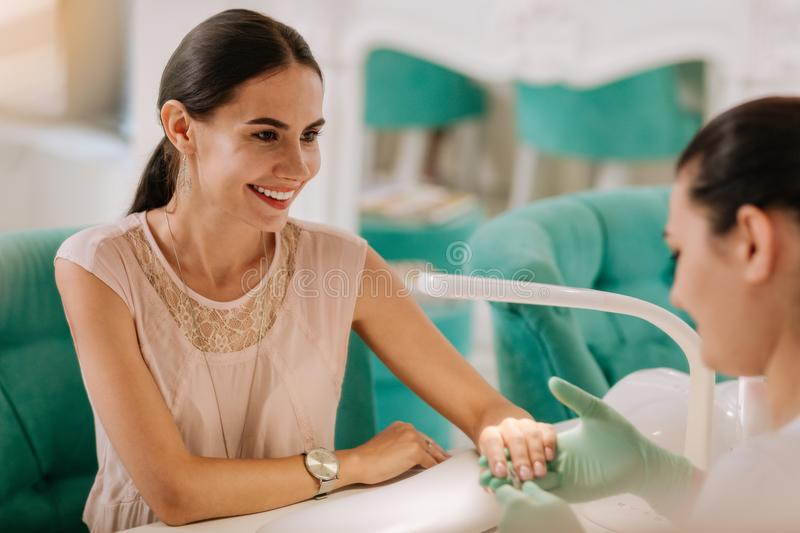 Beautiful elegant woman smiling while talking to nail master. Elegant woman. Beautiful elegant women wearing stylish clothes and accessories smiling while stock images