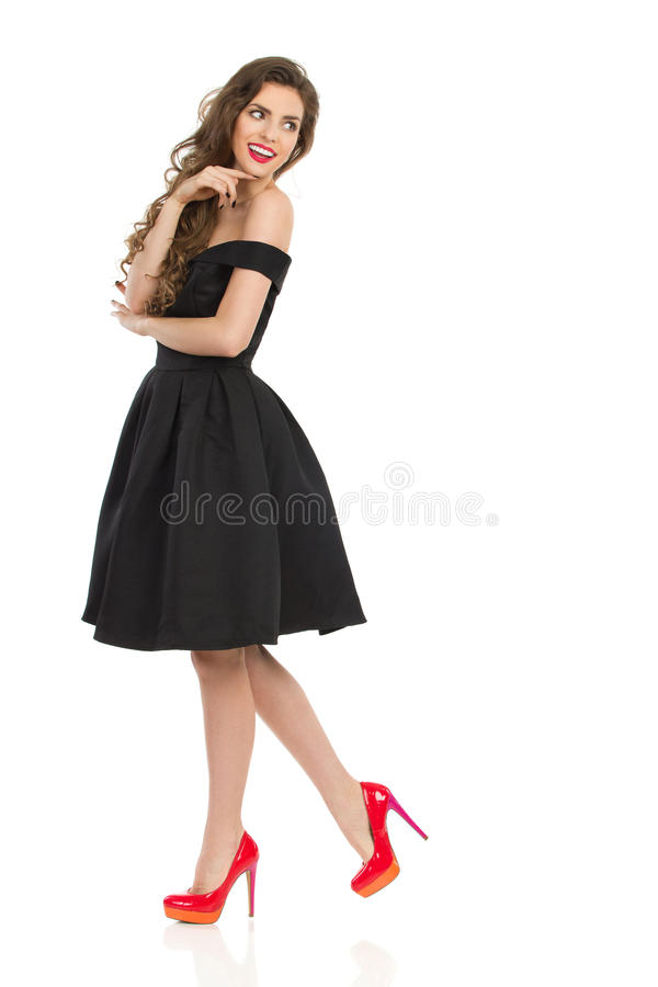 Elegant Woman In Black Cocktail Dress Is Looking Over Shoulder royalty free stock photos