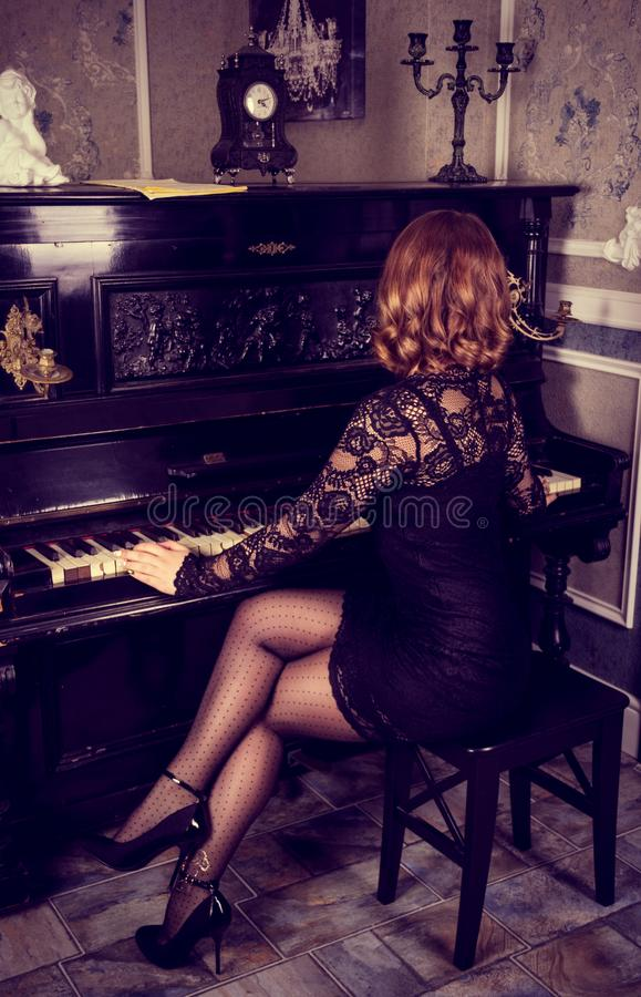 Elegant woman in black dress playing the piano. Beautiful female legs in stockings and heels. royalty free stock image