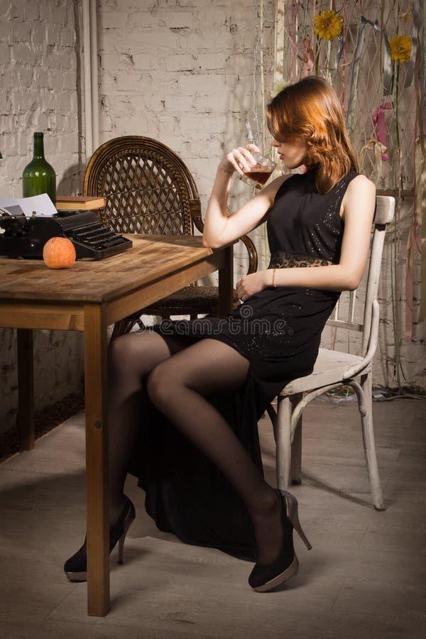 Elegant woman in black with the old typewriter. Elegant woman in black at the table with the old typewriter royalty free stock photo