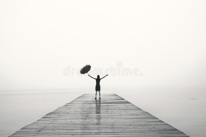 Elegant woman in black rejoices with their arms up in the rain. Woman in black rejoices with their arms up in the rain royalty free stock photos
