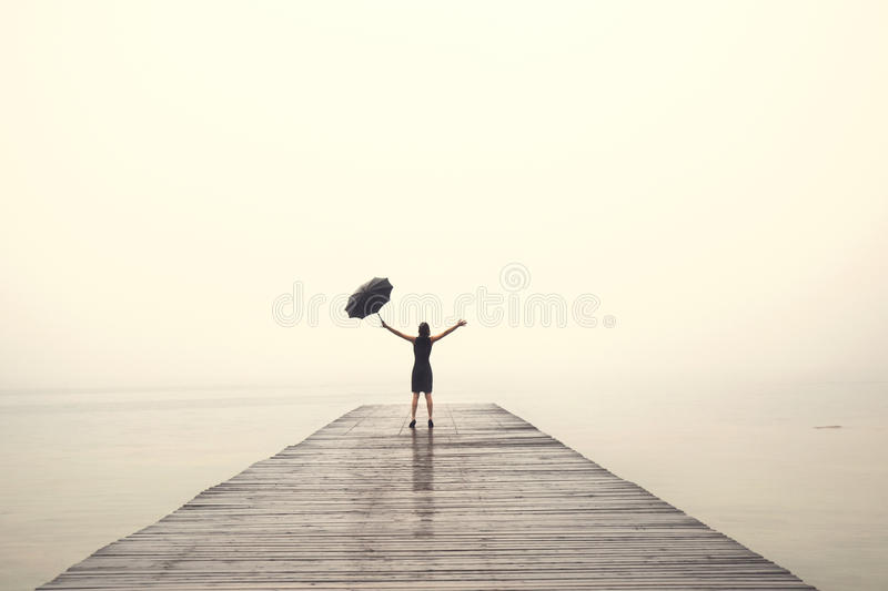 Elegant woman in black rejoices with their arms up in the rain royalty free stock photo