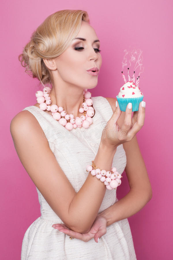 Elegant woman blowing out candles on birthday cake. Studio portrait over pink background royalty free stock photography
