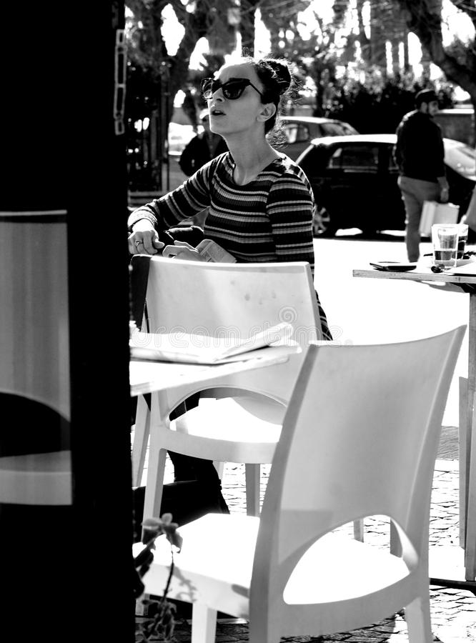 An elegant woman. Civitavecchia Rome Italy A beautiful girl with glasses portrayed while sitting at a table in an outdoor bar on a beautiful sunny day stock image